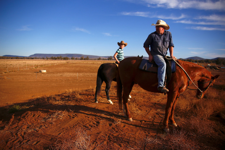 Image: Farmer Scott Cooper and his daughter Charlie ride their horses along a fence in a drought-effected paddock on their property named 'Nundah', located south of the central New South Wales town of Gunnedah