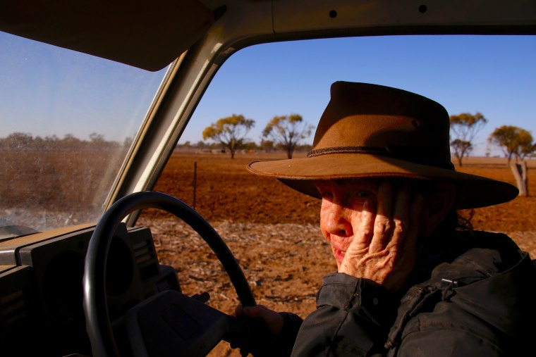 Image: Farmer May McKeown reacts as she drives her truck to feed the remaining cattle on her drought-effected property, located on the outskirts of the north-western New South Wales town of Walgett