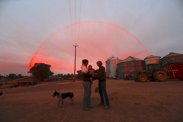 Image: Farmer Tom Wollaston's wife Margo talks with her daughter Natasha and her granddaughter Abbey as a rainbow forms above them at sunset on their drought-effected property, located west of the town of Tamworth