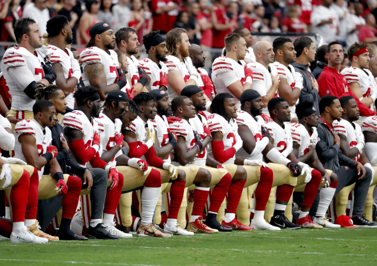 Image: Members of the San Francisco 49ers kneel during the national anthem