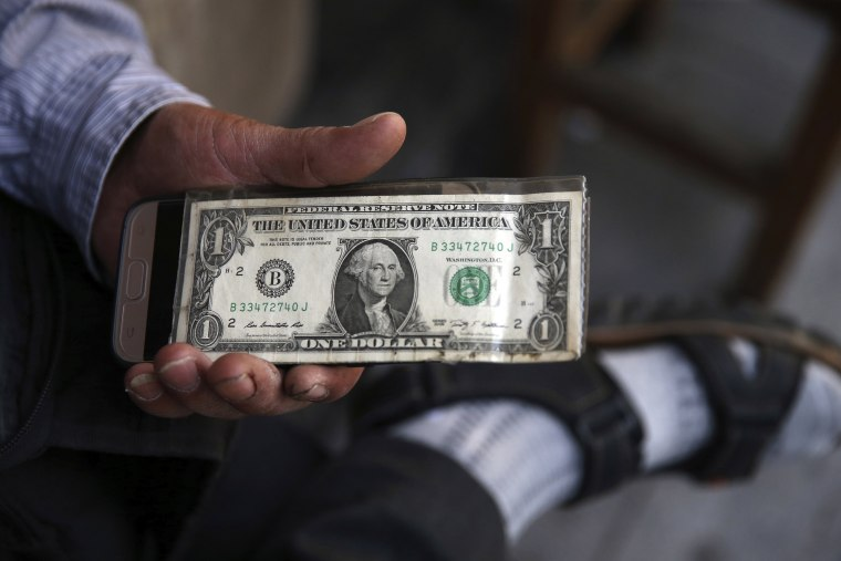 Image: An Iranian street money changer holds a U.S. banknote