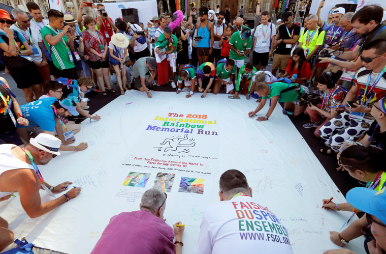 People sign a flag as they participate at the international Rainbow Memorial Run during the inauguration of the Gay Games village at the Hotel de Ville city hall in Paris