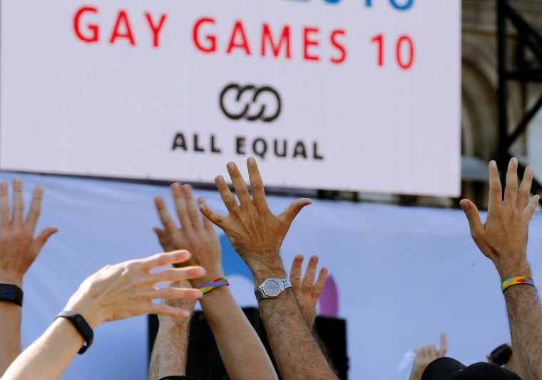 People react as they attend the inauguration of the Gay Games village at the Hotel de Ville city hall in Paris