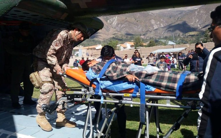 Image: A person is transported to a helicopter after eating contaminated food at a funeral in the Peruvian Andes, in Ayacucho