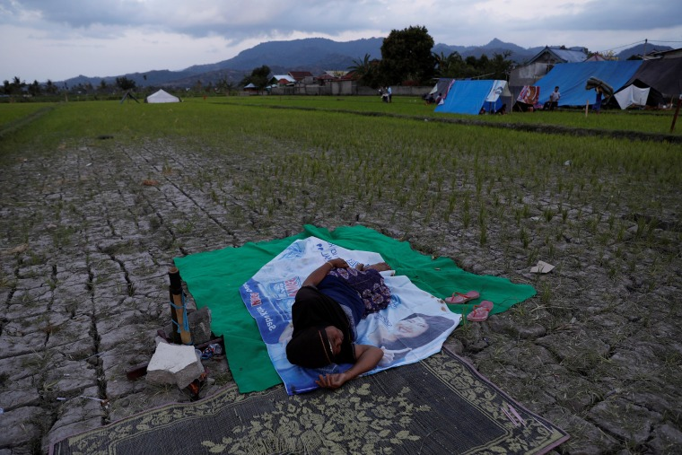 Image: A woman sleeps near her temporary tent near Tanjung hospital after earthquake hit on Sunday in North Lombok