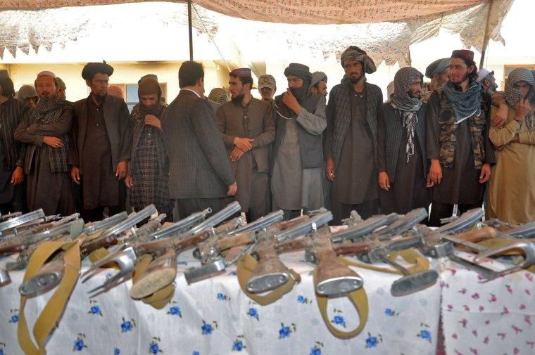 Image: Members of Islamic State hand over their weapons to the Afghan forces during a ceremony in Jawzjan province