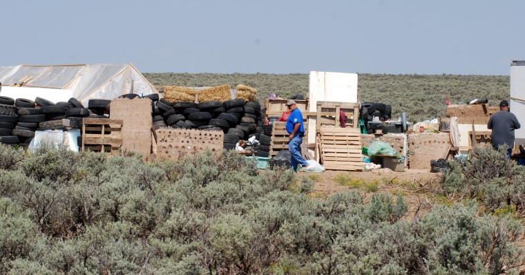 Image: A man walks through a compound in Amalia, New Mexico