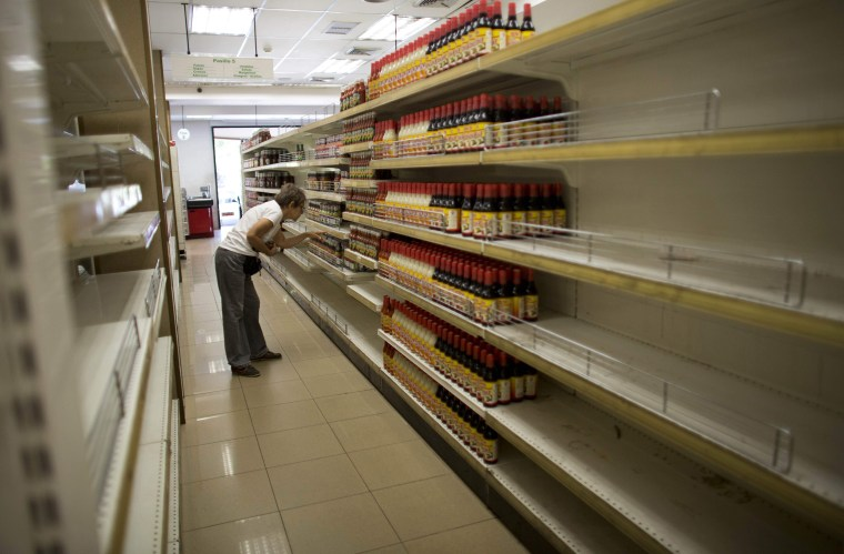 Image: A woman looks at products surrounded by empty shelves at a supermarket in Caracas