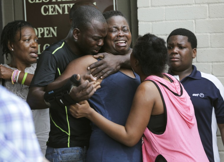 Image: The mother of two young children is comforted after she found them stabbed to death in their father's apartment