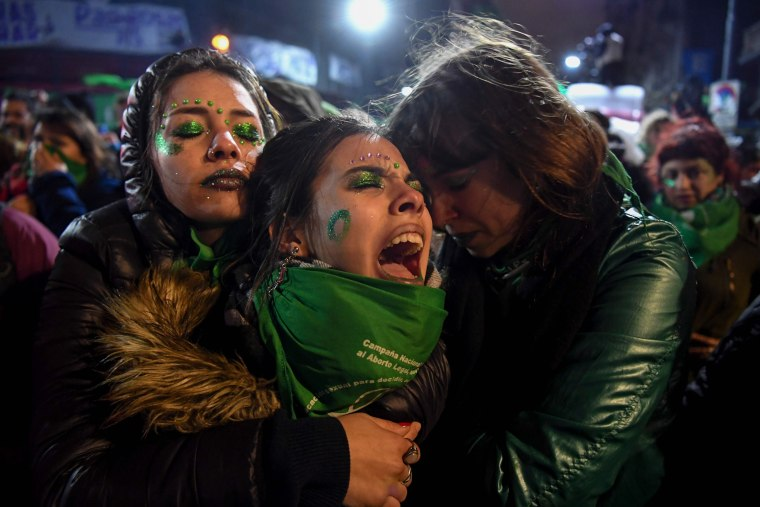 Image: Activists supporting the legalization of abortion comfort each other outside the National Congress in Buenos Aires