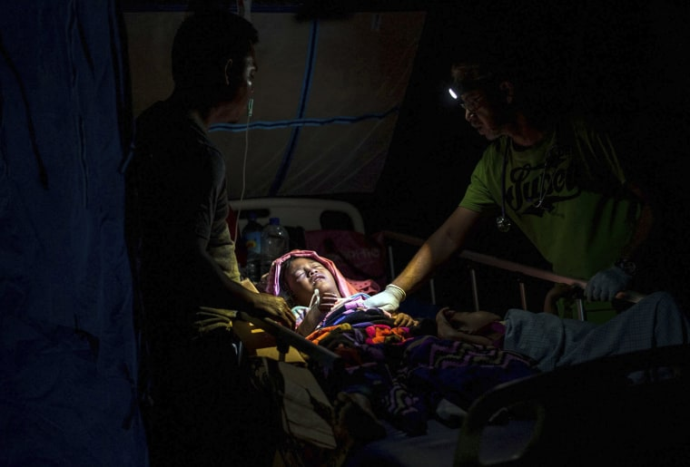 Image: A doctor examines children injured in the earthquake at a makeshift hospital in Tanjung on Lombok Island