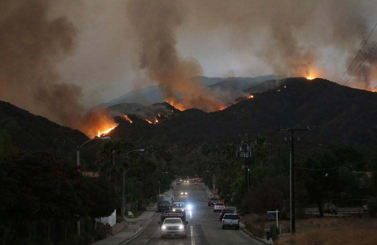 Image: Cars drive down a hill in a mandatory evacuation area as the Holy Fire burns in Cleveland National Forest