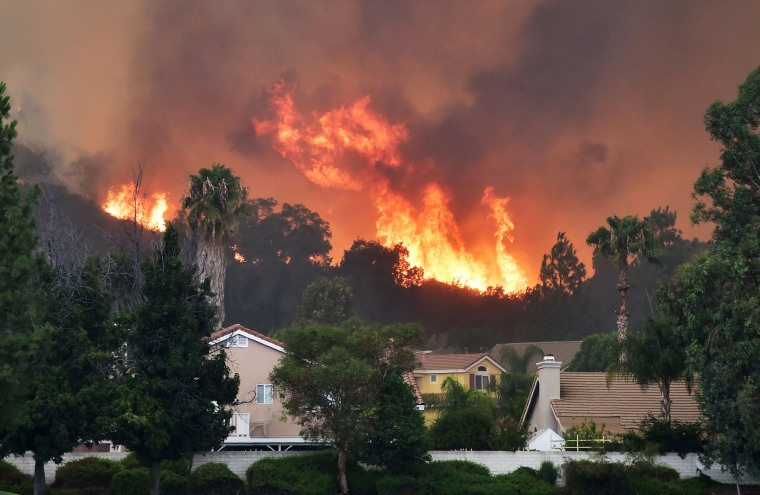 Image: Flames from the Holy Fire shoot up above homes in Lake Elsinore
