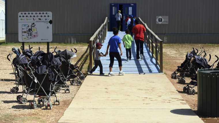 Image: Immigrants walk into a building at South Texas Family Residential Center in Dilley