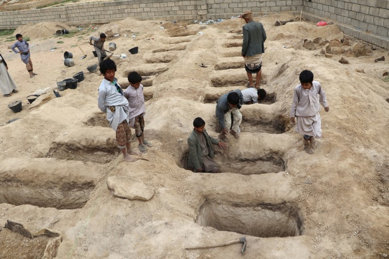 Image: Boys inspect graves prepared for victims of an air strike in the Saada province