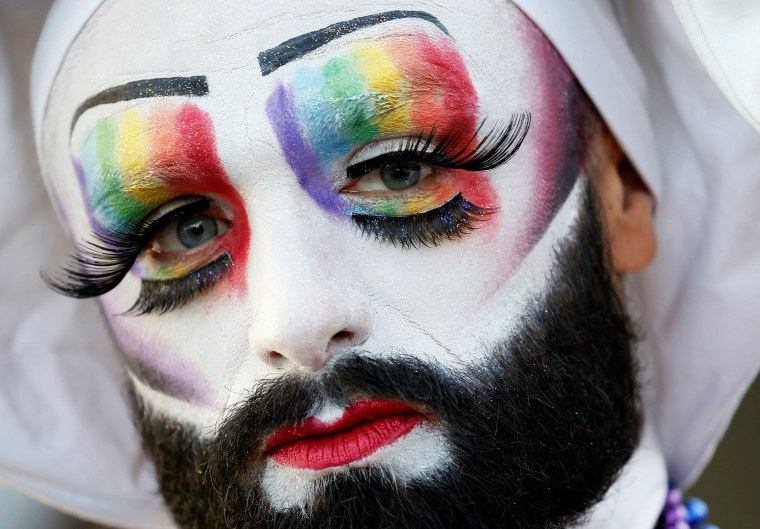 Image: A participant poses while attending the inauguration of the Gay Games village at the Hotel de Ville city hall in Paris