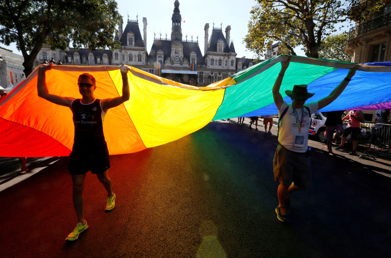 Image: People display a huge rainbow flag as they participate at the international Rainbow Memorial Run during the inauguration of the Gay Games village at the Hotel de Ville city hall in Paris