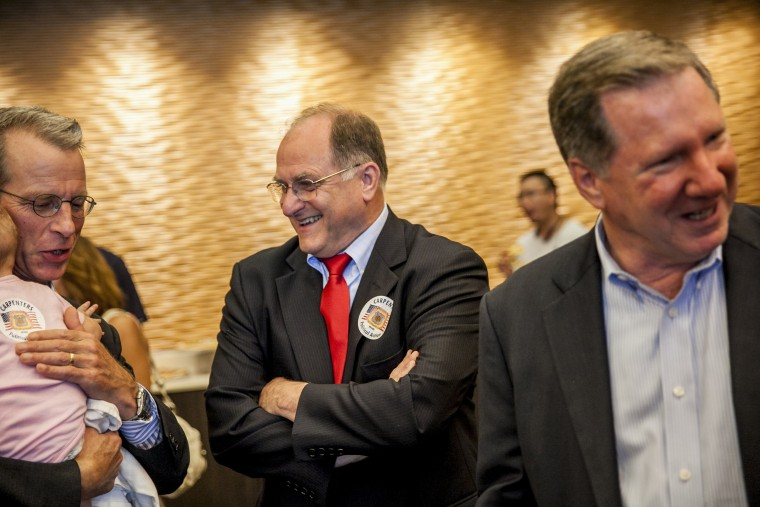 Image: Rep. Mike Capuano, center, talks to supporters during a campaign event