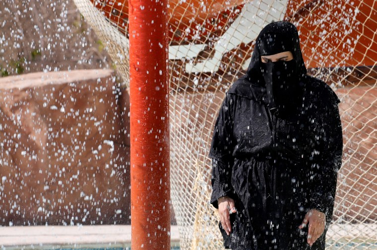 Image: A woman wearing a full veil (niqab) uses a shower to cool off in hot and humid weather inside an Aqua arena during summer holidays at El Ain El Sokhna in Suez, east of Cairo