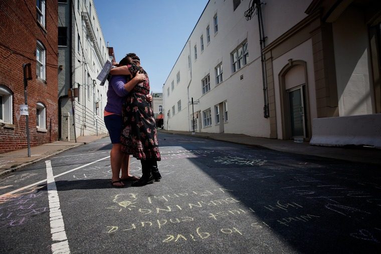 Image: Jenn Franklin, left, and Gretchen Burgess, who were at the deadly clash in Charlottesville last year, embrace