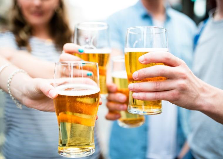 Image: Friends drink pints of beer at Oktoberfest