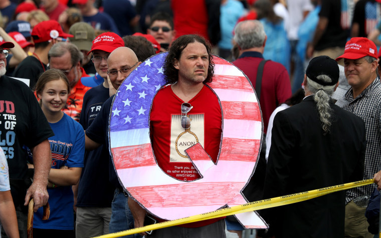"""Image: David Reinert holds a large \""""Q\"""" sign while waiting to see Trump"""