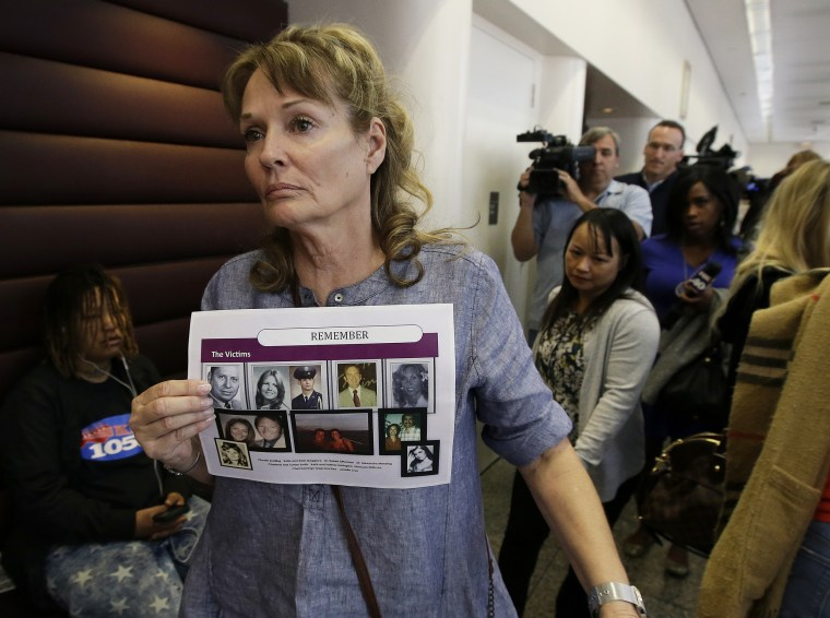Image: Melanie Barbeau displays photos of murder victims believed to be slain by the Golden State Killer