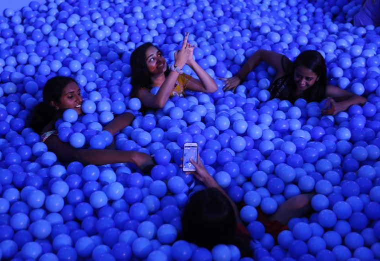 Image: Friends take pictures together in the ball pit at Dream Machine