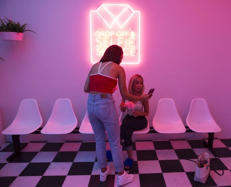 Image: Briana Miranda shows a photo to Lezly Velez
