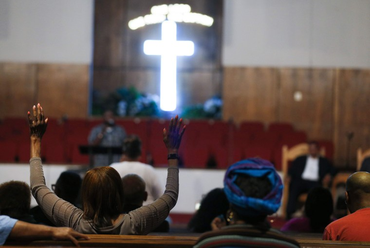 People pray at a morning service for singer Aretha Franklin.