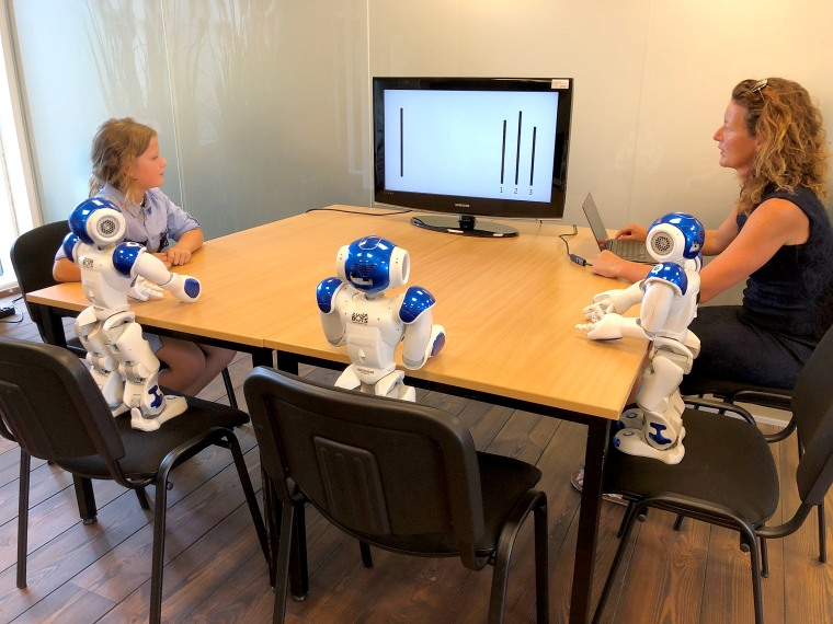 The experimental setup using the Asch paradigm with children and a group of robots.
