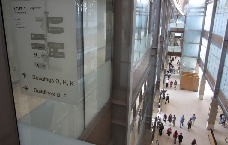 Visitors stroll through a long, glass-walled corridor that connects a dozen buildings at the new Rocky Mountain Regional VA Medical Center in Aurora, Colorado, after a ribbon-cutting ceremony at the hospital on July 21, 2018.