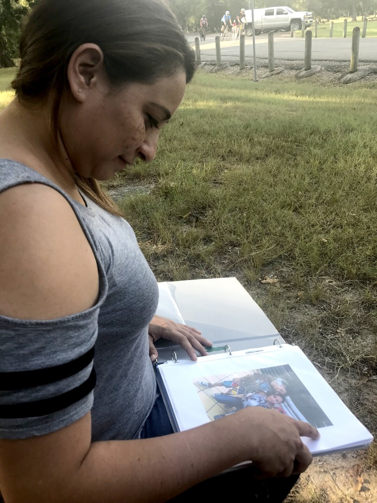 Raquel, who has been separated from her sons since the end of June, looks at photos of them.