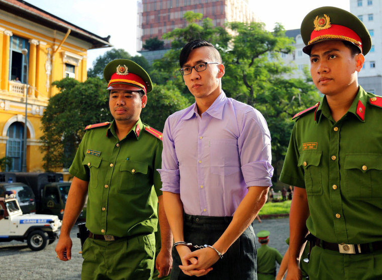 Image: US citizen Will Nguyen is escorted by policemen before his trial at a court in Ho Chi Minh city