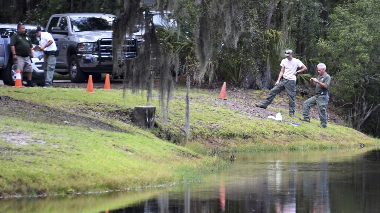 Law enforcement with S.C. Department of Natural Resources take pictures of the site where authorities say Cassandra Cline was dragged into a lagoon by an alligator on Aug. 20, 2018, on Hilton Head Island, South Carolina.