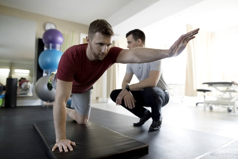 Male physiotherapist guiding client balancing in clinic gym