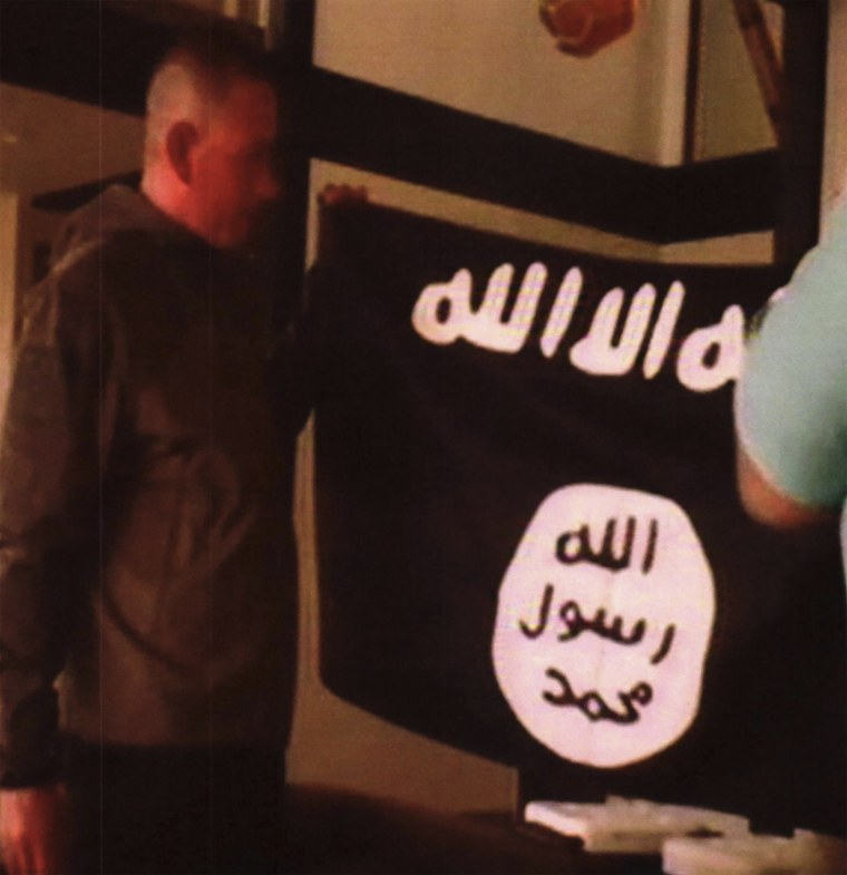 Army Sgt. 1st Class Ikaika Kang holds an Islamic State group flag after allegedly pledging allegiance to the group