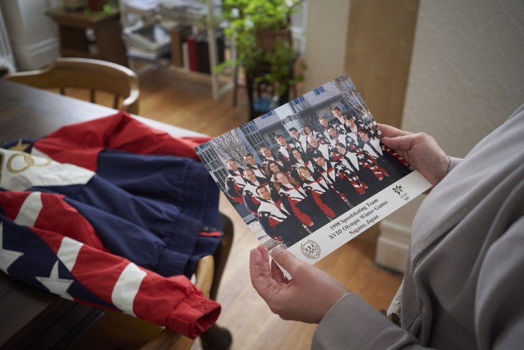 Image: Kirstin Holum, who is now known as Sister Catherine, holds a photo of the 1998 U.S. Olympic speedskating team