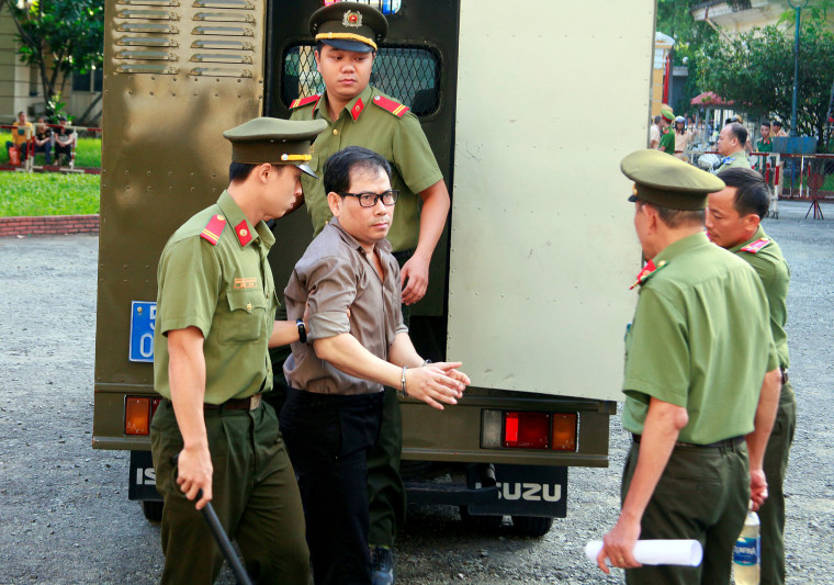 Image: U.S. citizen James Nguyen is escorted by police to a court before his trial in Ho Chi Minh city