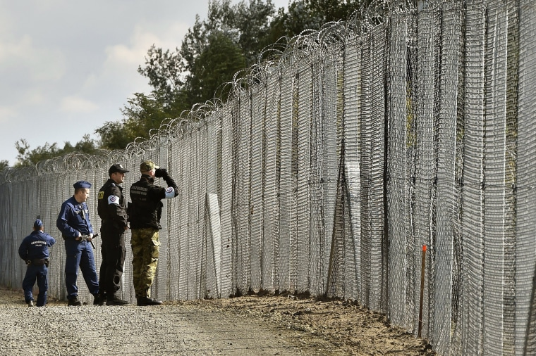 Image: Police officers and border guards patrol a fence at the Hungarian-Serbian border