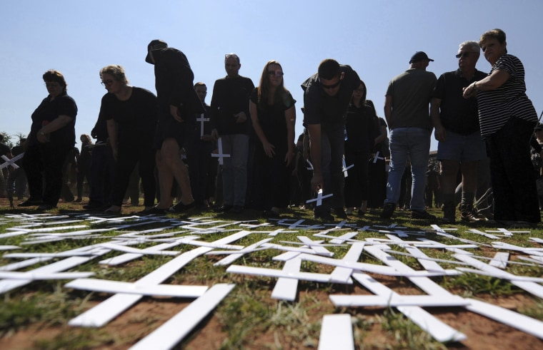 Image: People place white crosses, symbolically representing farmers killed in the country, at a ceremony at the Vorrtrekker Monument in Pretoria