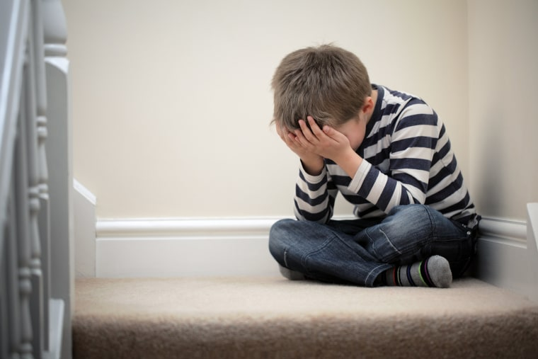 Image: Upset problem child sitting on staircase