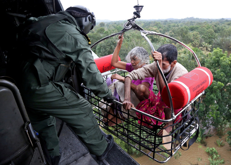 Image: People are airlifted by the Indian Navy soldiers during a rescue operation at a flooded area in the southern state of Kerala
