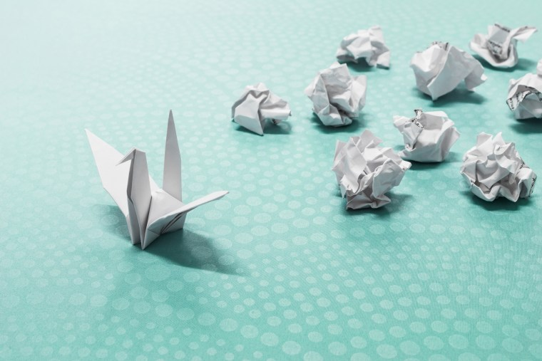 Success concept, A origami paper bird and crumpled paper balls
