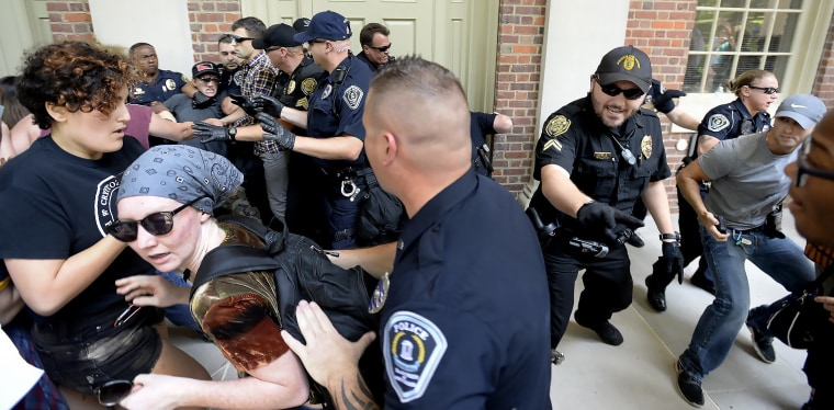 Image: Protesters scuffle with police during a rally in front of Graham Memorial Building on the campus of UNC in Chapel Hill
