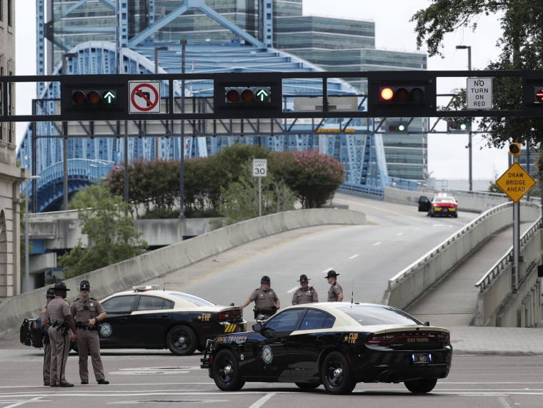 Image: Florida Highway patrolmen block the entrance to the Main Street Bridge near the scene of a mass shooting at Jacksonville Landing