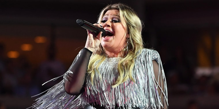 Kelly Clarkson dazzles in silver fringe and sparkles at the US Open.