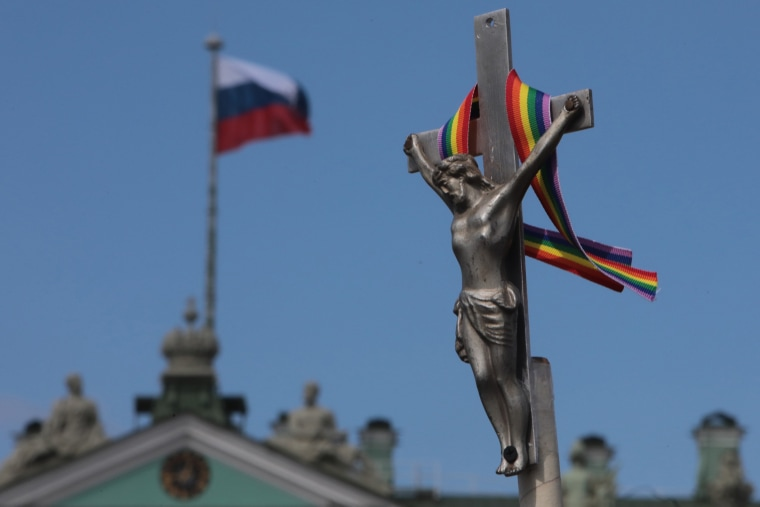 Image: A rainbow-colored ribbon tied to a crucifix is seen next to a Russian flag