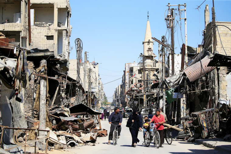 People walk in a street during a media tour in Douma near Damascus