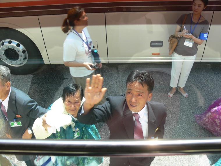 Image: Chung Hak-soon's sister-in-law and nephew wave goodbye to her outside the bus that will take her back to South Korea